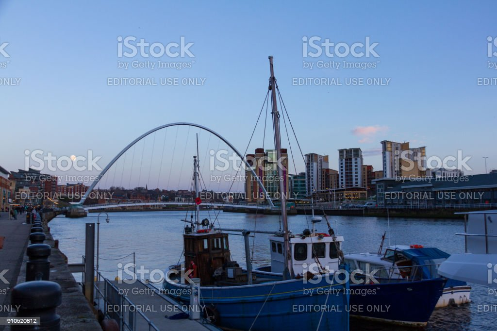 Newcastle Quayside with Gateshead Millenium Bridge and Boat in sight stock photo
