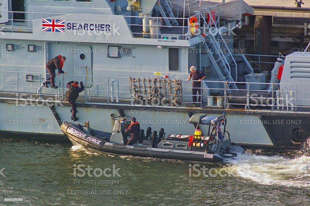 Newcastle, United Kingdom - October 5th, 2014 - UK border force officers boarding a RIB patrol boat alongside the border force cutter HMC Searcher stock photo