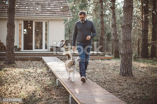 Mature men at home with pet dog during pandemic isolation.