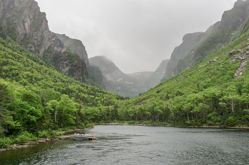 a picnic table floats on a pontoon in Gros Morne National Park's Western Brook Pond, Newfoundland, Canada in the place where hikers disembark from a boat to hike into the Long Range Mountains, with a misty and cloudy sky