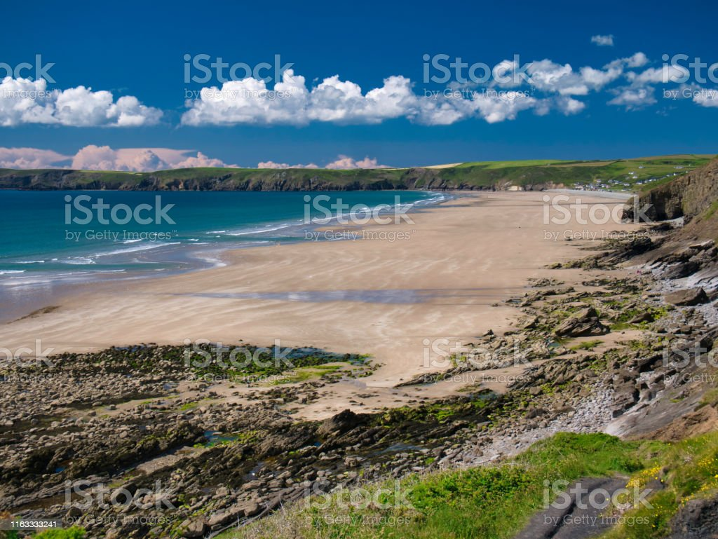 Newgale Beach in Pembrokeshire, Wales, UK on a summer day with blue...