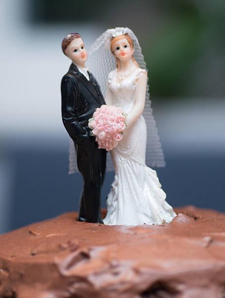 newleywed auf schokoladenbrauner kuchen - tortenfiguren stock-fotos und bilder