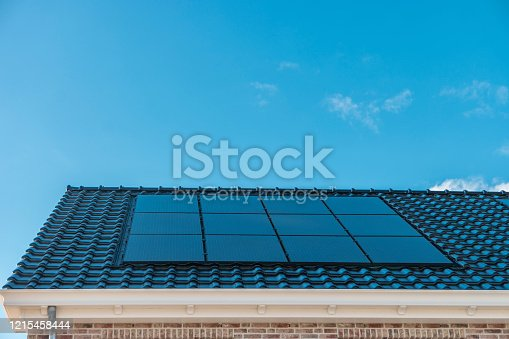 Newly build house in the Netherlands with solar panels attached on the roof against a sunny sky of new building black solar panels Flevoland