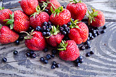Newly collected Fresh blueberries and strawberries on wooden background. Agriculture, gardening, harvest, healthy lifestyle concept. Summer organic berry over wood.