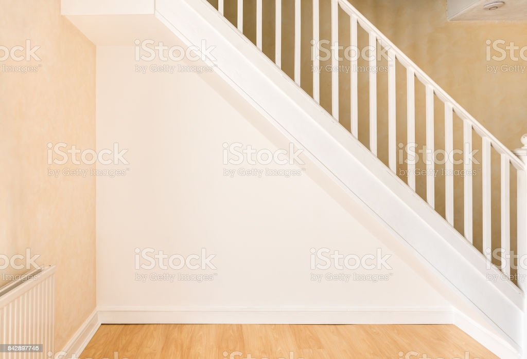 Newly decorated wall under staircase in a domestic room. stock photo