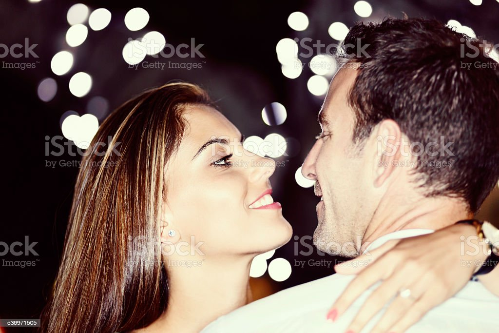 Newly engaged couple smile into each other's eyes. It's love! stock photo