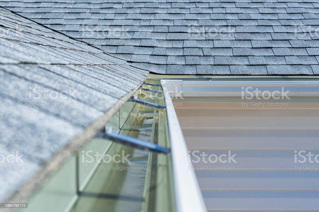 Neu installierte Regenrinnen und Bitumenschindeln auf ein Wohnhaus – Foto