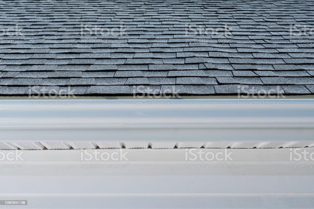 Neu installierte Regenrinnen, Faszie, Untersicht und Asphalt Schindeln auf einem Wohnhaus – Foto