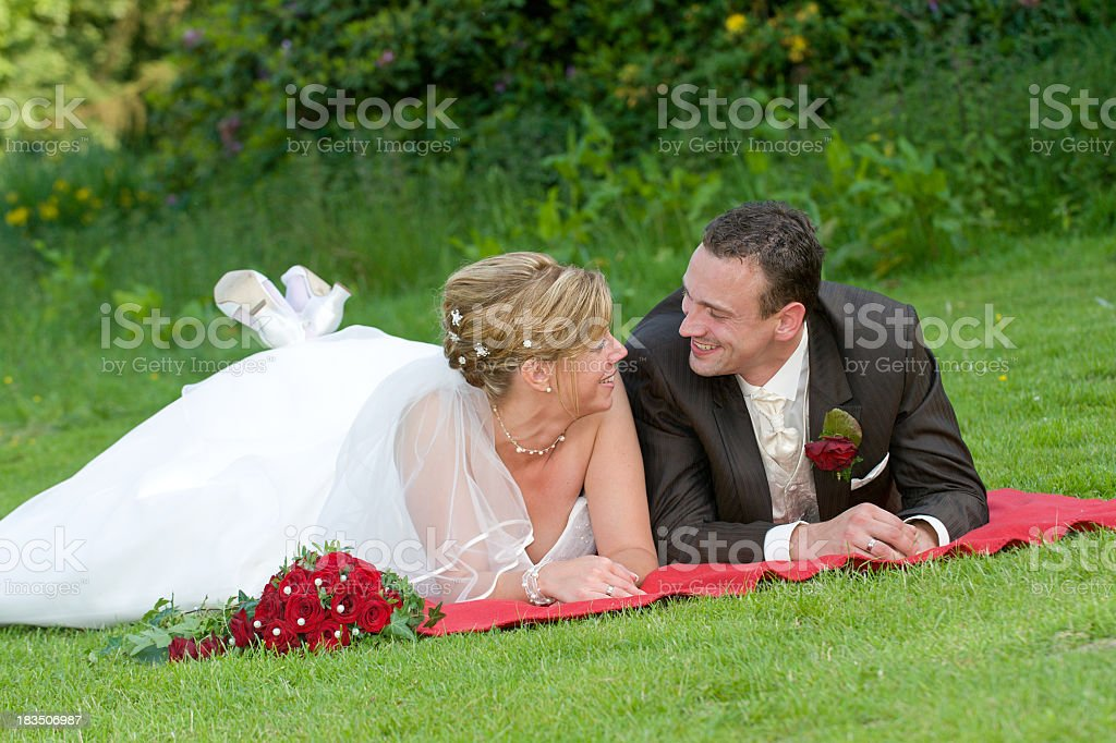 Newly married bride and groom are happy on the meadow stock photo