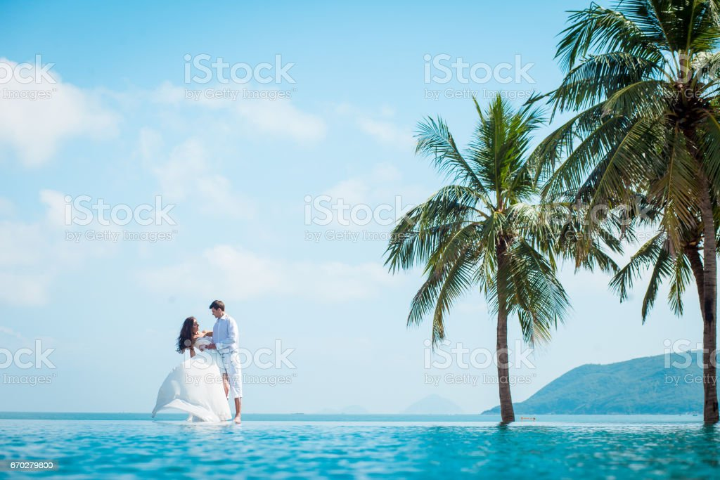 Newly married couple after wedding in luxury resort. Romantic bride and groom relaxing near swimming pool. Honeymoon. stock photo