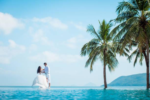 frisch verheiratetes paar nach der hochzeit im luxus-resort. romantische braut und bräutigam in der nähe von schwimmbad entspannen. flitterwochen. - traum pools stock-fotos und bilder