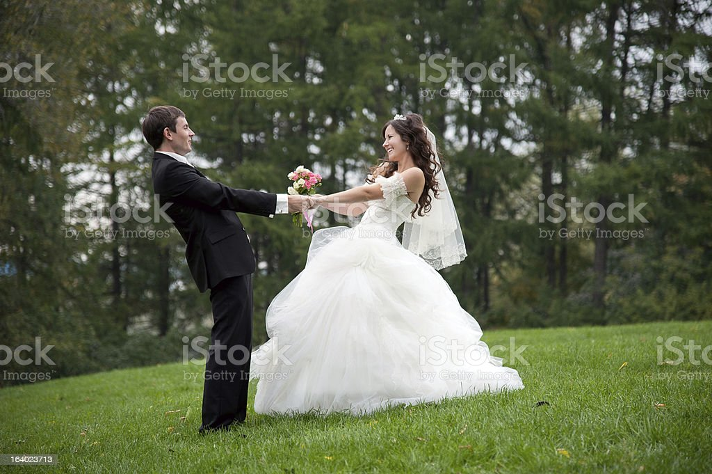 Newly married couple dancing in field stock photo