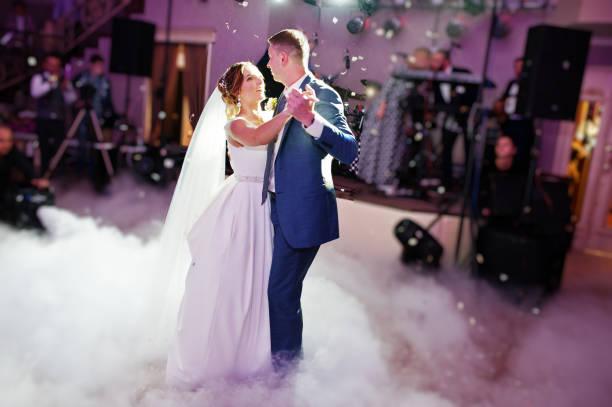 newly married couple dancing on their wedding party with heavy smoke and multicolored lights on the background. - sala balowa zdjęcia i obrazy z banku zdjęć