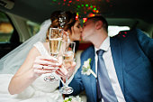 Newly married couple drinking champagne in the limousine on their wedding day.