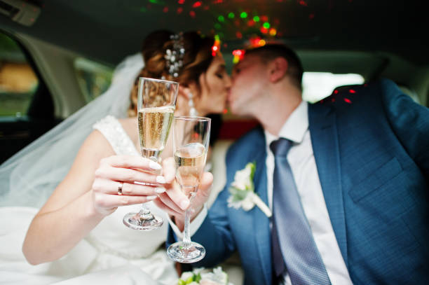 Newly married couple drinking champagne in the limousine on their wedding day. stock photo