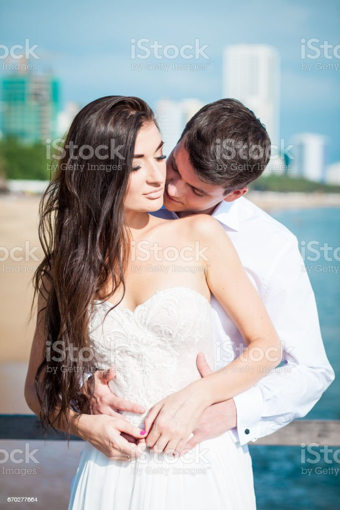 d2fab68370f Newly married couple kiss each other after wedding in luxury resort. Romantic  bride and groom relaxing near swimming pool. Honeymoon. - Stock image .