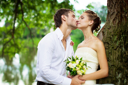 674214372 istock photo Newly married couple kissing in the park near a tree 174791948