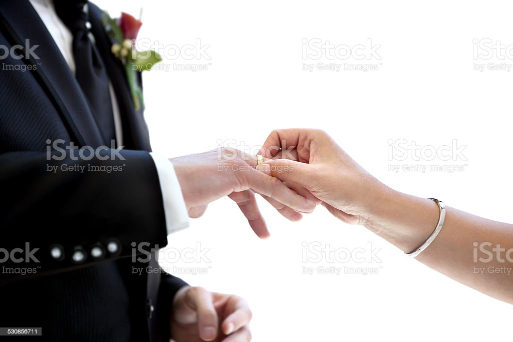 newly married couple putting wedding ring on the finger stock photo