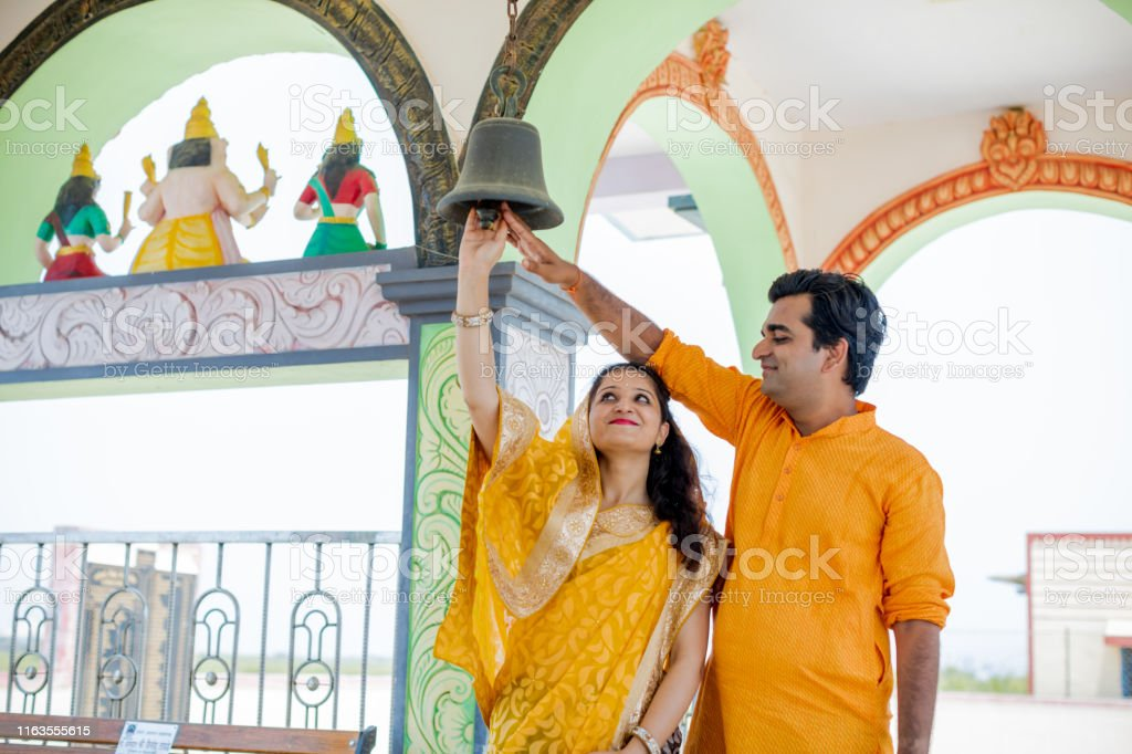 Newly Married Hindu Couple Visiting A Temple For Prayers