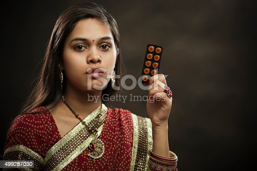 istock Newly married Hindu young woman holding sachet of medicine tablets. 499287030
