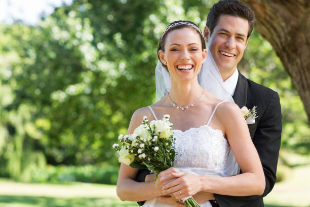 Newly wed couple with flower bouquet in park Portrait of newly wed couple with flower bouquet in park bridegroom stock pictures, royalty-free photos & images