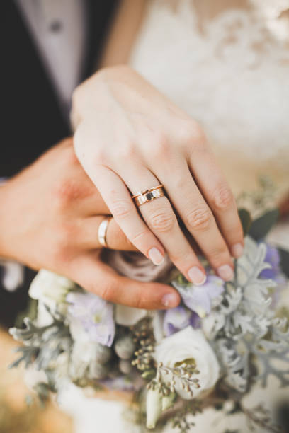Newly wed couple's hands with wedding rings stock photo