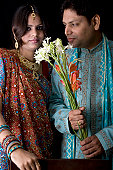 istock Newly Wed Indian Asian Couple vertical dark portrait with flowers 116424049