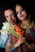 istock Newly Wed Indian Asian Couple vertical dark portrait with flowers 172702654