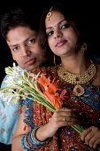 istock Newly Wed Indian Asian Couple vertical dark portrait with flowers 172721126