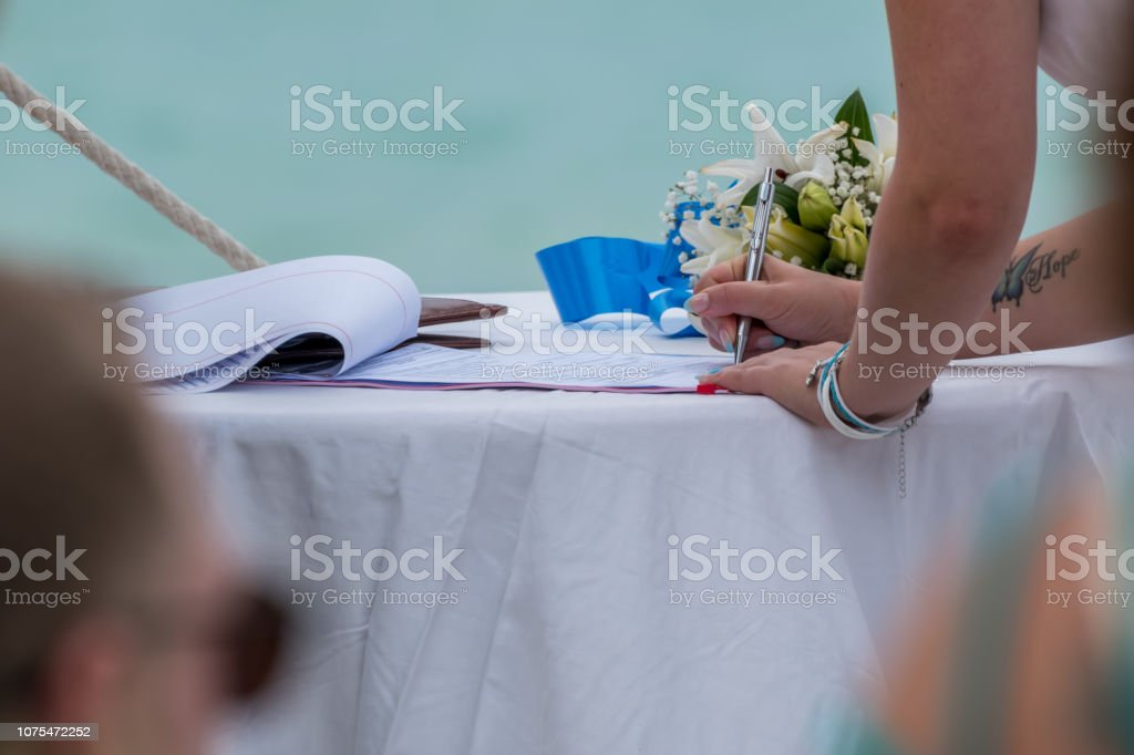 Newly weds signing legal documents stock photo