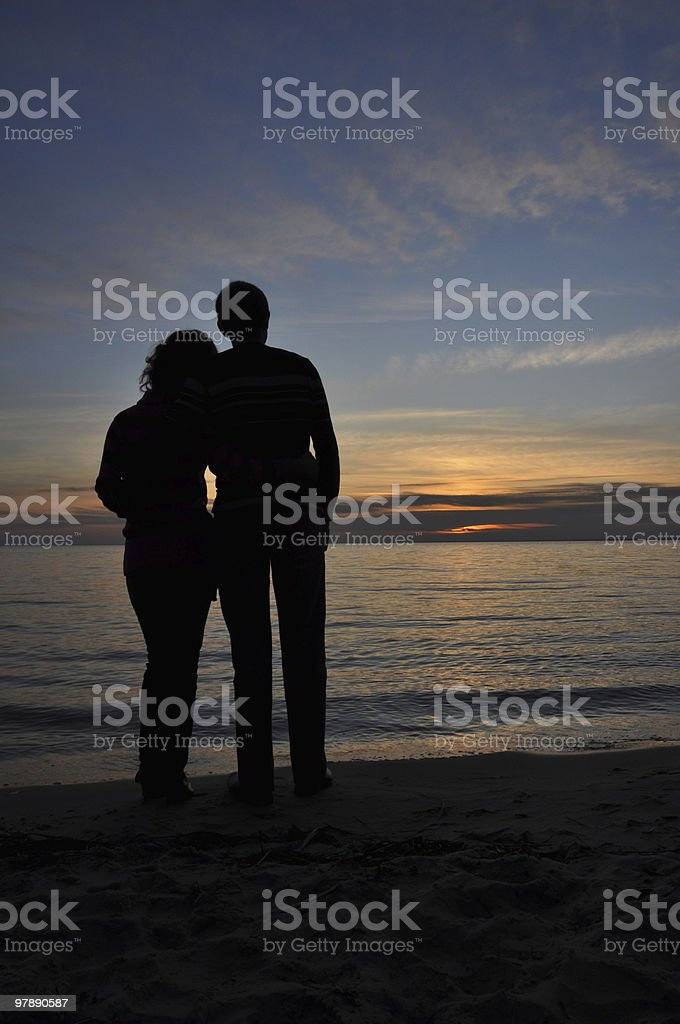 Newly weds standing on the seashore and watching sunset royalty-free stock photo