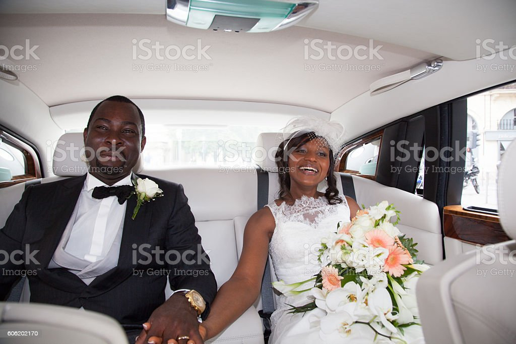 Newlywed african couple sitting in the car stock photo