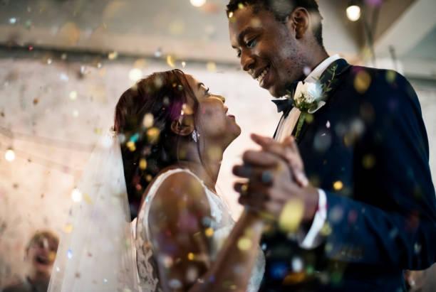 casal de descendência africana recém-casado dançando a celebração do casamento - casamento - fotografias e filmes do acervo