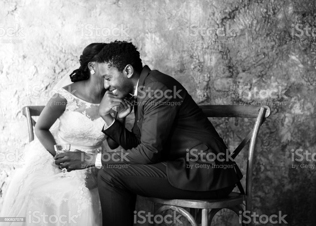 Newlywed african ethnicity couple whispering a message stock photo