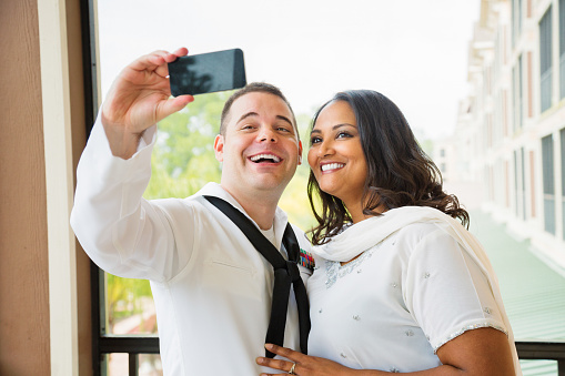 Newlywed American sailor shooting selfie with his exotic wife