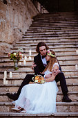 Newlywed husband and wife embracing and sitting on old Mediterranean stone steps at wedding reception