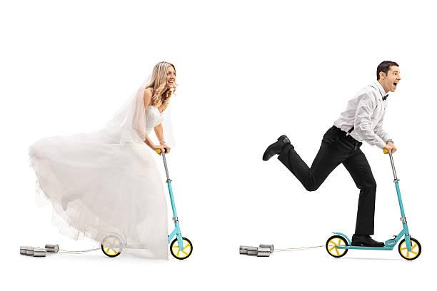 newlywed bride and groom riding scooters - zinn hochzeit stock-fotos und bilder
