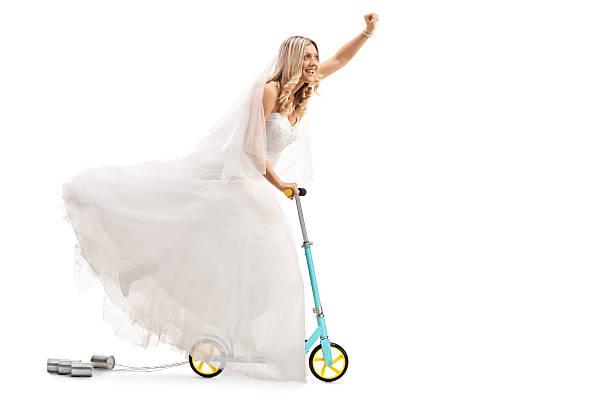 newlywed bride riding a scooter and gesturing with her hand - zinn hochzeit stock-fotos und bilder
