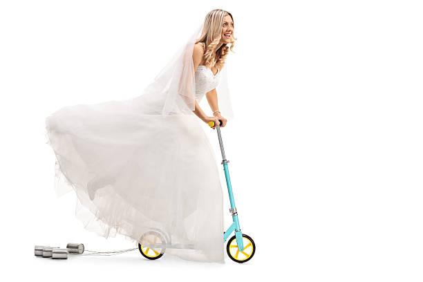 newlywed bride riding a scooter - zinn hochzeit stock-fotos und bilder