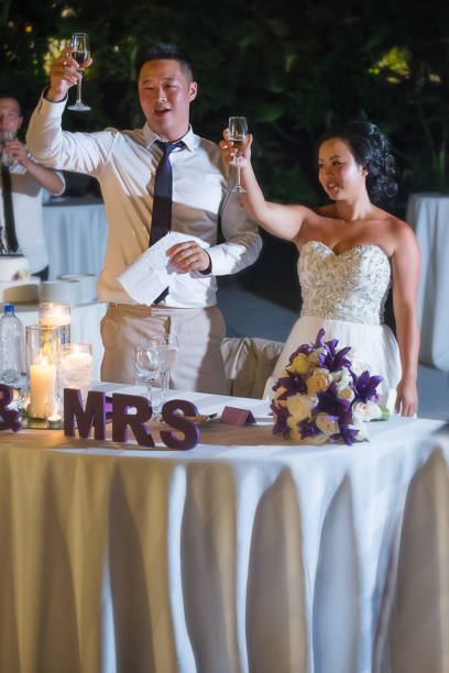 Newlywed cheering at reception Bride and groom holding wine glass chinese wedding dinner stock pictures, royalty-free photos & images