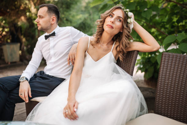 Newlywed coupe sitting on a sofa angry at each other in a middle of an argument. Young couple problem concept outdoor Newlywed coupe sitting on a sofa angry at each other in a middle of an argument. Young couple problem concept outdoor. bridegroom stock pictures, royalty-free photos & images