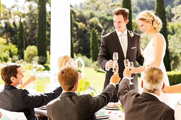 frisch verheiratet paar anstoßen und gäste zusammen am tisch - bräutigam tisch stock-fotos und bilder