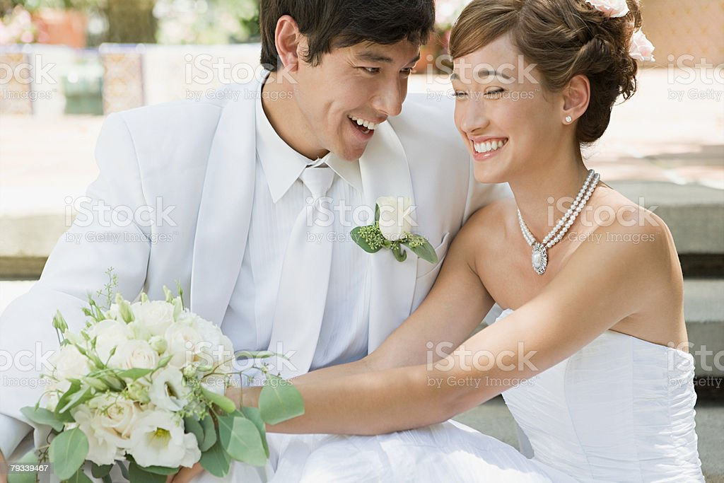 Newlywed couple holding a bouquet stock photo