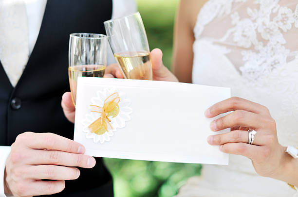 Newlywed couple holding invitation card and sparkling wine stock photo