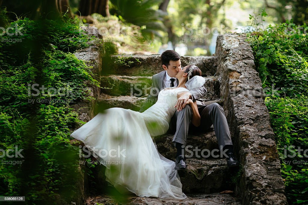 Newlywed couple kissing on some steps in the jungle stock photo