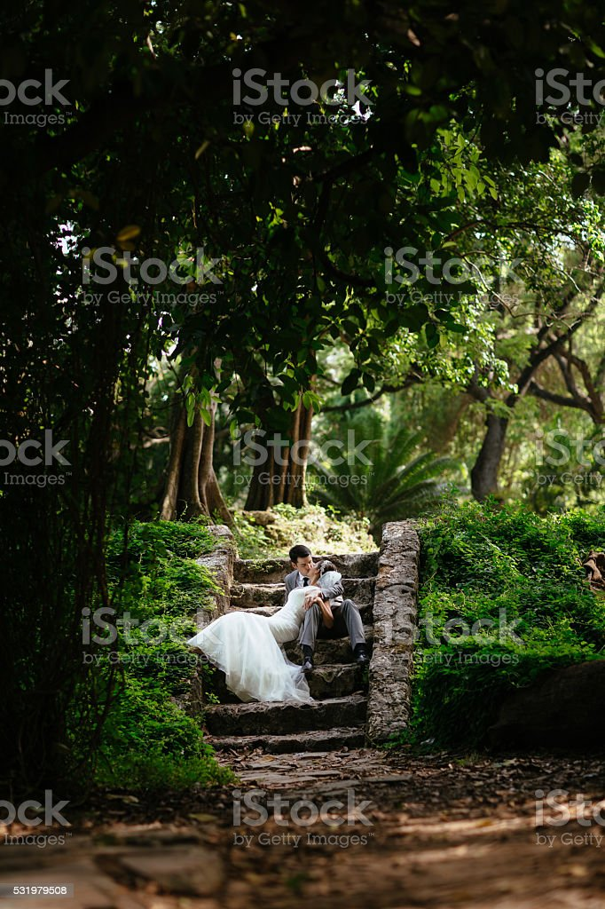 Newlywed couple laying together on the stairs stock photo