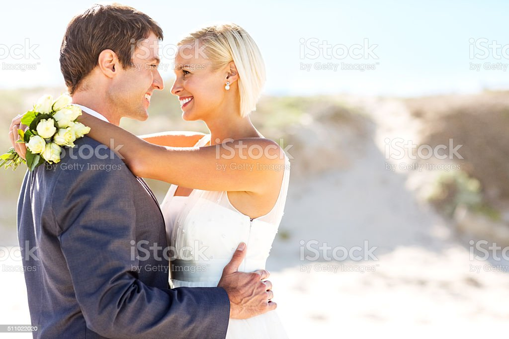 Newlywed Couple Looking At Each Other On Beach stock photo