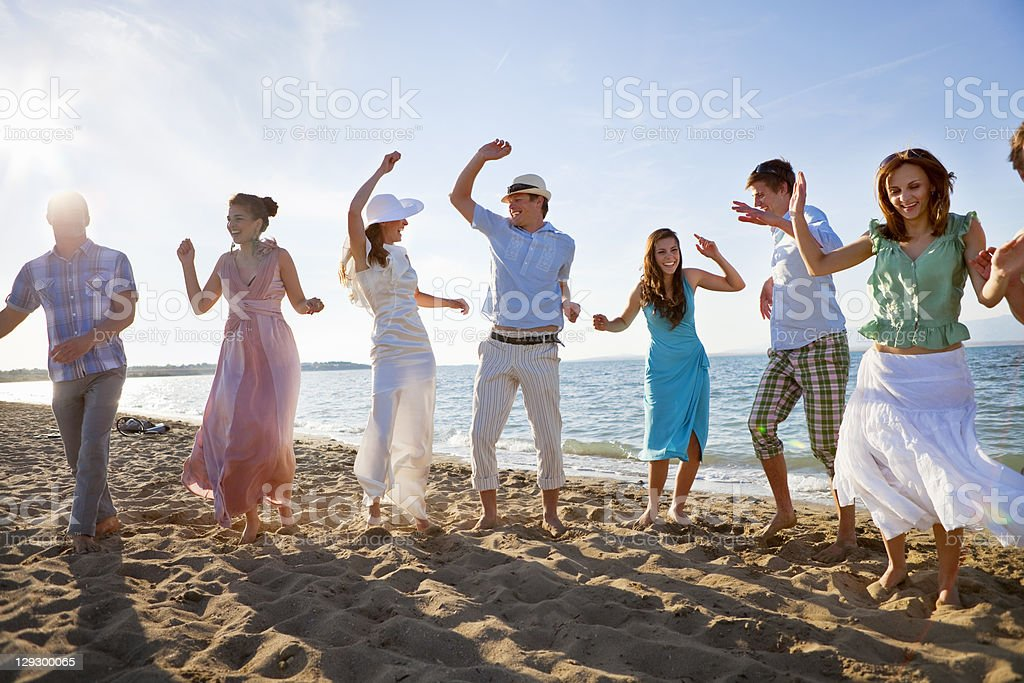 Newlywed couple on beach with friends stock photo