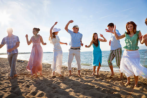 Newlywed couple on beach with friends  sun shining through dresses stock pictures, royalty-free photos & images