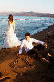 Newlywed couple on the beach.Groom sitting on sand and bride watching the sea behind him..